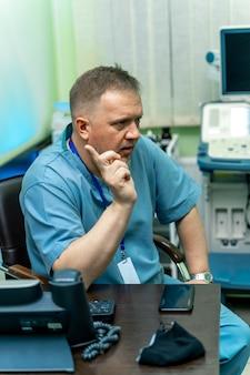 Echografie arts legt diagnose uit. zittend in de buurt van professionele apparatuur. diagnostiek. echografie. portret. detailopname
