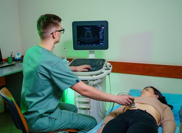 Echografie arts maakt een echografie van de buikholte van de vrouw. vrouw wordt onderzocht door een echoscopiste.