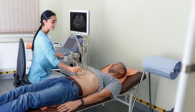 Echografie diagnose van de maag op de buikholte van een man in de kliniek, vergrote weergave.