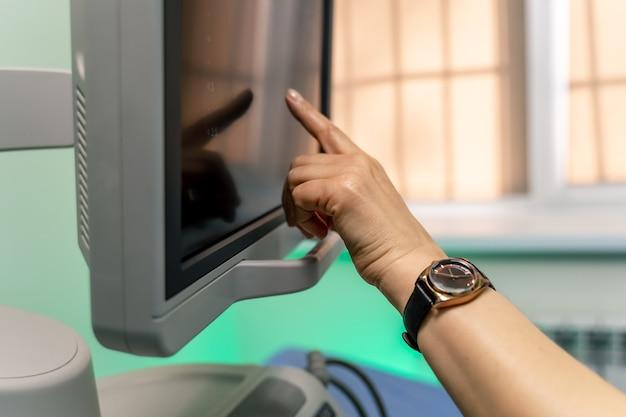 Echografiemonitor in medische ruimte. vrouw s hand wijzend op het scherm. bijgesneden foto.
