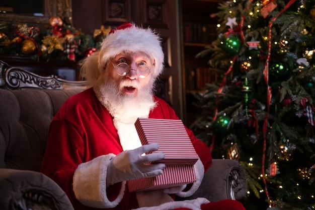 Echt authentiek verrast santa claus houdt kerstcadeau. vervulling van verlangens. santa zit op