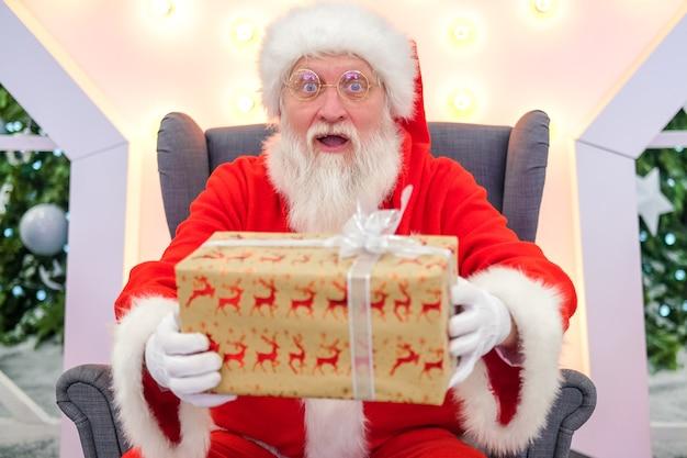 Echt authentiek verrast santa claus santa houdt kerstcadeau voor. vervulling van verlangens.