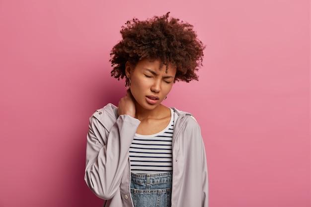 Echt gestresste ongelukkige vrouw met afro-kapsel, raakt nek, lijdt aan pijn