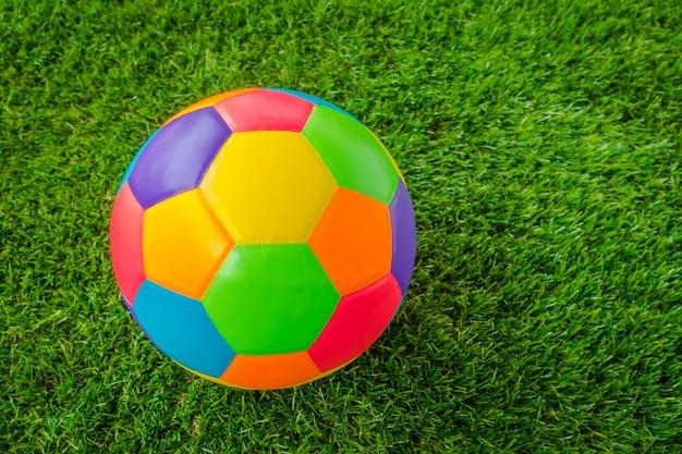 Echt lederen kleurrijke multi color voetbal bal op het groene gras.
