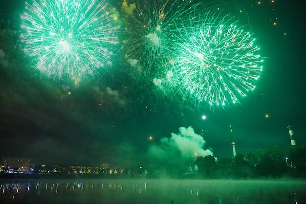 Echt vuurwerk over de nacht stad en water. grote groene salvo's.