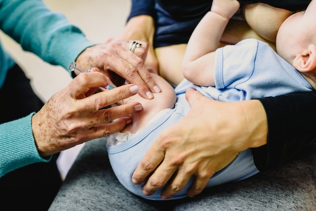 Echte baby wordt gevaccineerd met een spuit in de dij door een kinderarts om de verspreiding van ziekten te voorkomen.