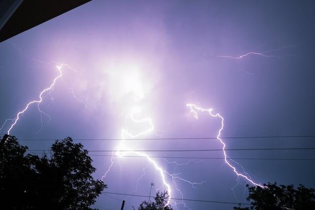Echte bliksemschicht in de stad tijdens een storm, gezien vanuit huisraam