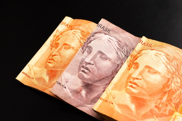 Echte brl braziliaanse geldbankbiljetten geïsoleerd op donkere ondergrond
