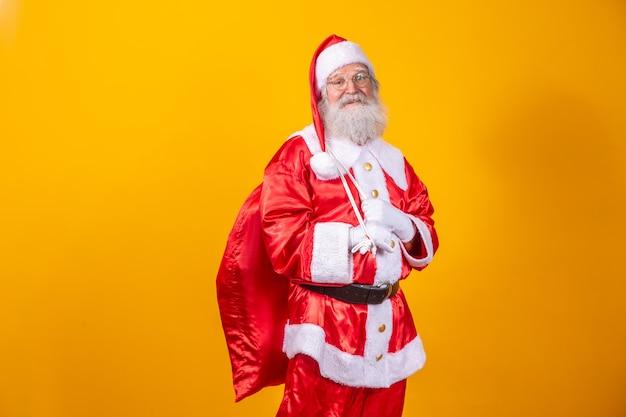 Echte kerstman met een rode achtergrond, met een bril, handschoenen en een hoed die naar de zijkant kijkt.