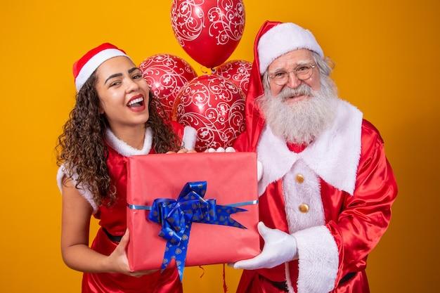 Echte kerstman met zijn noelete-helper die het kerstcadeau van het kind vasthoudt