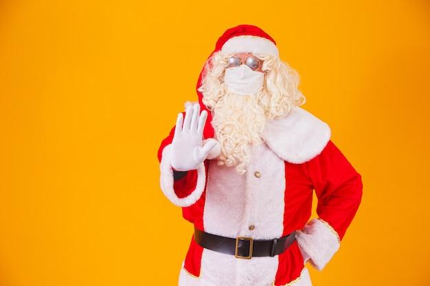 Echte kerstman op gele achtergrond, met een beschermend masker tegen de covid19. kerst met sociale afstand. covid-19