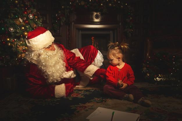 Echte kerstman speelt met kinderen in de buurt van de kerstboom.