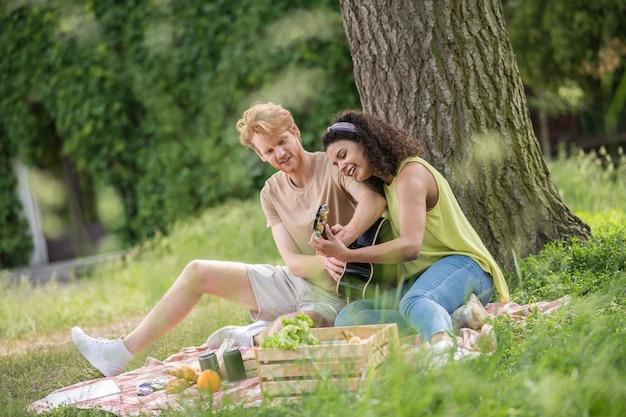 Echte leven. jonge vrolijke geïnteresseerde roodharige man en mulat vriendin met gitaar die interessante vrije tijd doorbrengt op picknick in het park