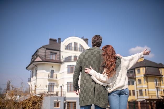 Echte leven. knuffelende man in trui en vrouw met lang rood haar die met de rug naar de camera staat te kijken naar hun nieuwe huis