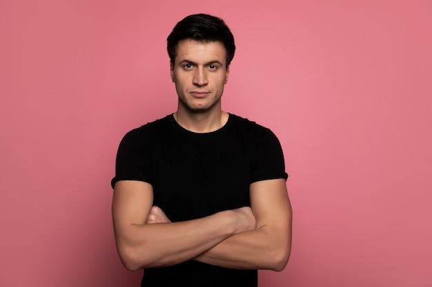 Echte man. aantrekkelijke jonge man in een zwart t-shirt, die met gevouwen armen staat en met een doordringende blik in de camera kijkt.