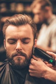Echte mannenverzorging. close-up van knappe man die baardkapsel krijgt door kapper bij barbershop