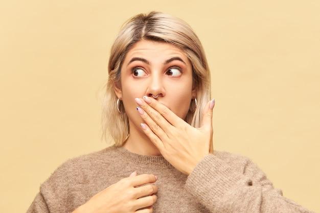 Echte menselijke emoties, gevoelens en reacties. aantrekkelijke blonde jonge vrouw die verbaasde blik heeft, probeert geheime of vertrouwelijke informatie te bewaren, mond bedekt met hand en weg kijkt
