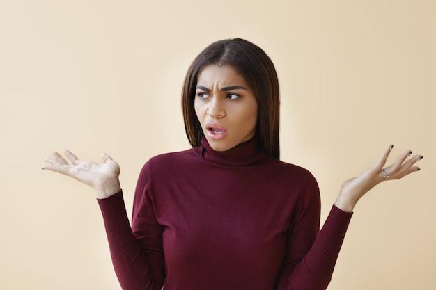 Echte menselijke emoties, reacties en gevoelens. portret van een ontevreden mooie jonge afro-amerikaanse vrouw die verontwaardigd zijn handen opheft en de mond wijd openzet, verloren voor woorden, uitroepend: wat !?
