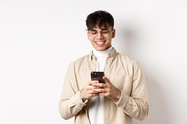 Echte mensen. natuurlijke jongeman bericht lezen op mobiele telefoon, glimlachend en kijken naar smartphonescherm, staande op een witte muur.