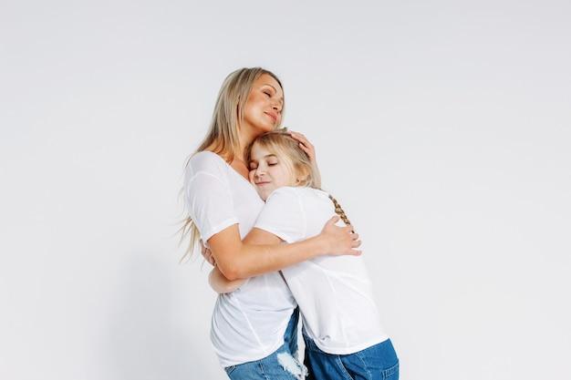 Echte moeder en dochter in witte t-shirts en jeans knuffelen geïsoleerd op een witte achtergrond