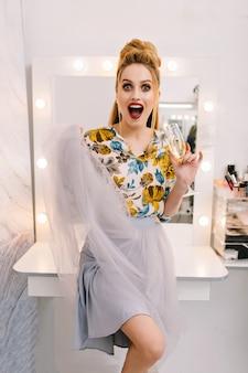 Echte positieve emoties uitdrukken van modieus mooi model in tule rok, met luxe kapsel, make-up, glas champagne in kapsalon