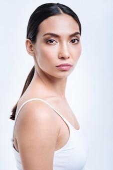 Echte schoonheid. het portret van een charmante donkerharige jonge vrouw in een witte tanktop die half gedraaid staat terwijl ze op een witte muur wordt geïsoleerd