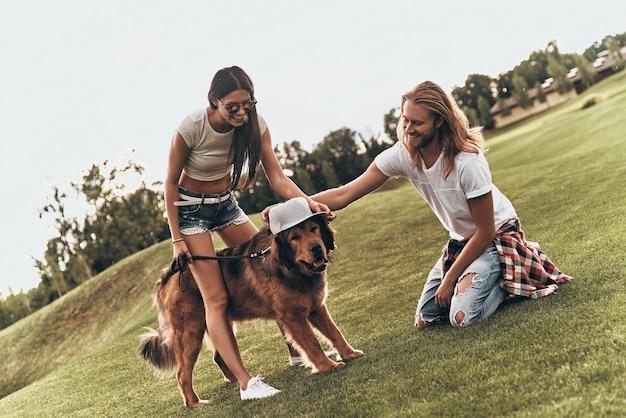 Echte stijl. knappe jonge man die een hoed op de hond zet terwijl hij zorgeloze tijd doorbrengt met zijn vriendin buitenshuis