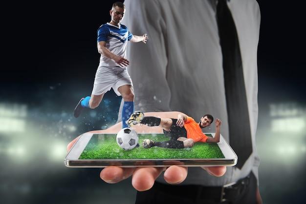 Echte voetballers die tijdens een wedstrijd op een mobiele telefoon worden weergegeven