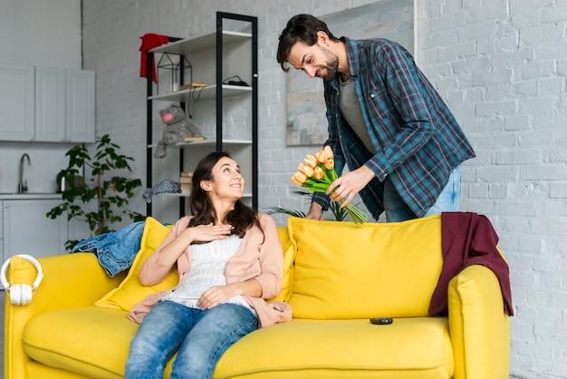 Echtgenoot die bloemen geeft aan haar vrouw in woonkamer