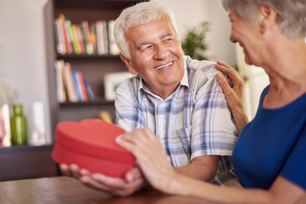 Echtgenoot die een hartvormig cadeau aan zijn vrouw geeft