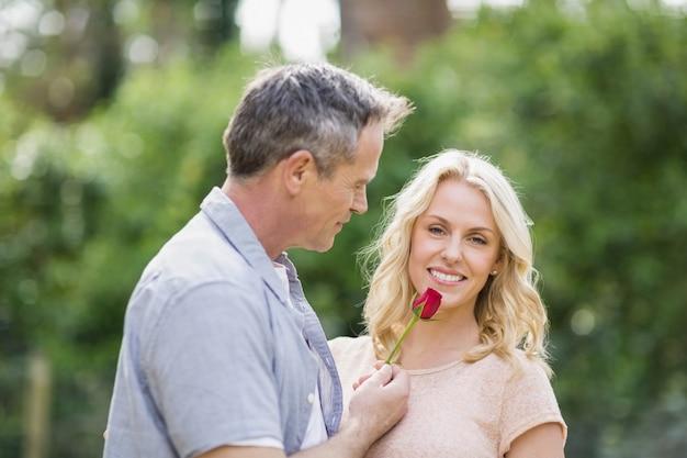 Echtgenoot die een roos aan vrouw aanbiedt buiten in het bos