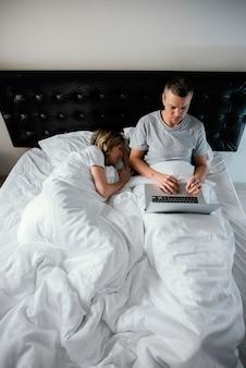 Echtgenoot die laptop met behulp van terwijl de vrouw slaapt