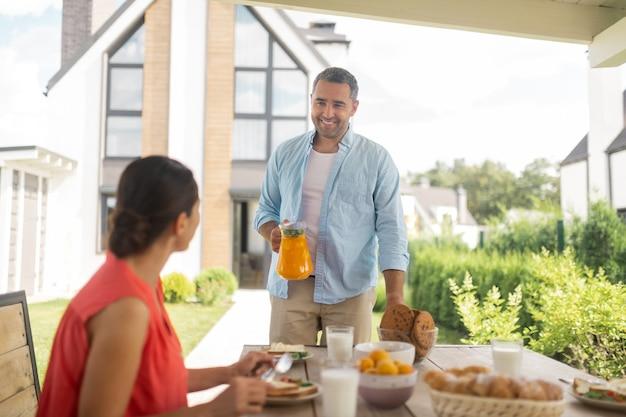 Echtgenoot die sap brengt. zorgzame glimlachende man die wat sinaasappelsap meeneemt voor het ontbijt met zijn vrouw buiten