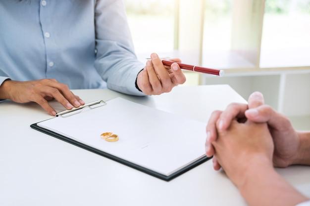 Echtgenoot en echtgenote lezen scheidingsovereenkomst en vatten een pen bij tot het ondertekenen van het decreet