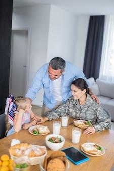 Echtgenoot knuffelen. zorgzame liefhebbende echtgenoot knuffelt zijn vrouw die in de strijdkrachten dient en dochter