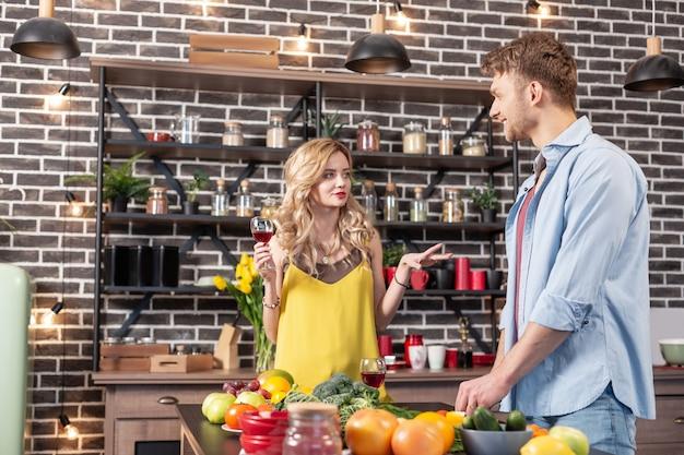 Echtgenoot koken. bebaarde man die salade kookt en praat met zijn aantrekkelijke geliefde die rode wijn drinkt
