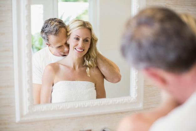 Echtgenoot kussende vrouw op de hals in de badkamers