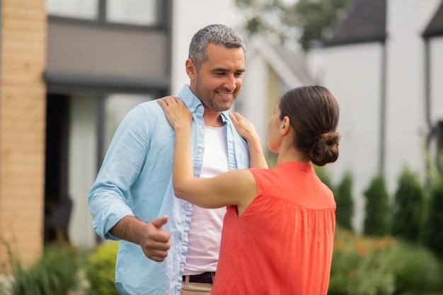 Echtgenoot lachend. man lacht tijdens het dansen met vrouw buiten in de buurt van huis in het weekend