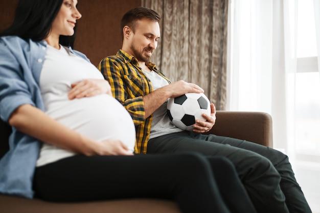 Echtgenoot met bal en zijn zwangere vrouw met buik grappen thuis, humor. zwangerschap, prenatale periode. aanstaande mama en papa rusten op de bank, gezondheidszorg