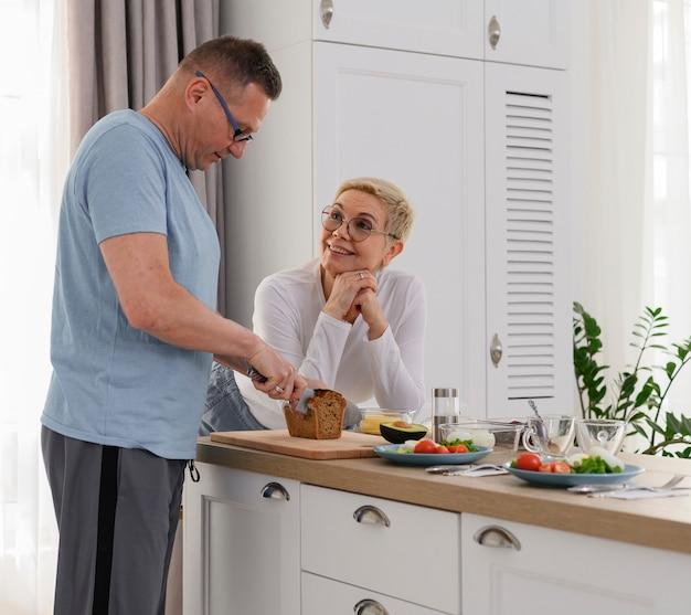 Echtgenoot op middelbare leeftijd die diner kookt voor zijn vrouw ideale relatieportret van gelukkig paar