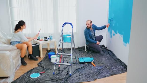 Echtgenoot veranderende muurverf met rolborstel. vrouw met kwast. appartement make-over. paar in huisdecoratie en renovatie in gezellige flat, reparatie en make-over