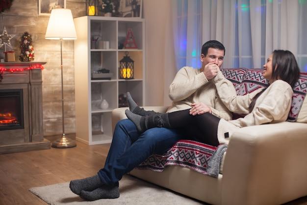 Echtgenoot zittend op de bank met haar mooie vrouw die haar hand kust om kerstmis te vieren.