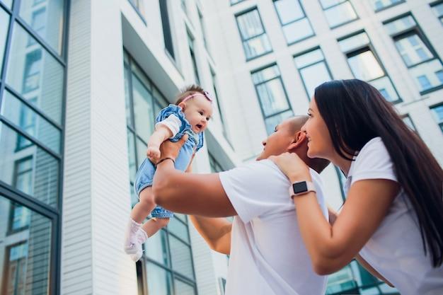 Echtpaar, aman met kind, vrouw met man op zijn schouders. tegen de achtergrond glasbouw