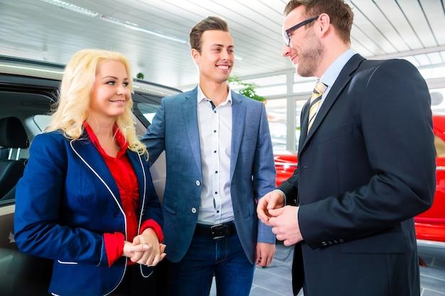 Echtpaar auto kopen bij dealer en adviserende verkoper