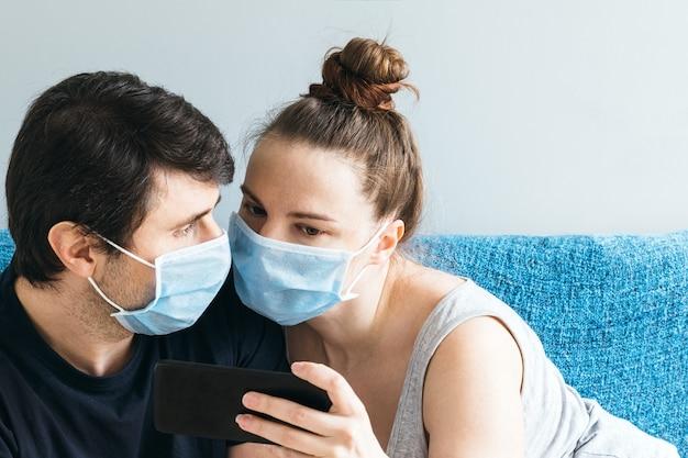Echtpaar dat met blauwe medische gezichtsmaskers een smartphone bekijkt