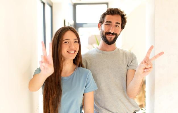 Echtpaar glimlacht en kijkt gelukkig, zorgeloos en positief, gebaren overwinning of vrede met één hand
