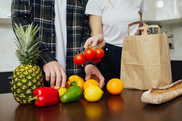 Echtpaar haalt het uit aankopen die ze in de supermarkt hebben gekocht om de lunch in de keuken te koken.