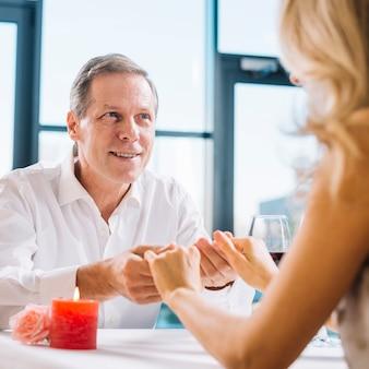 Echtpaar hand in hand tijdens romantisch diner