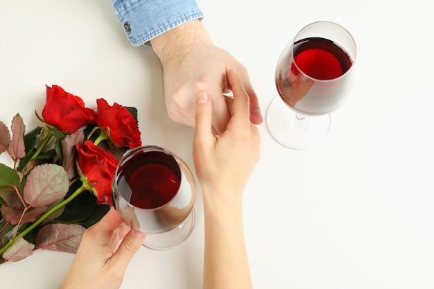 Echtpaar handen, wijn en rozen op witte achtergrond