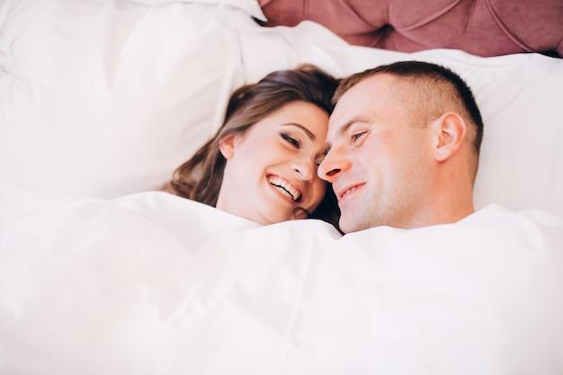 Echtpaar in bed. gelukkig meisje en vriendje onder de dekens.
